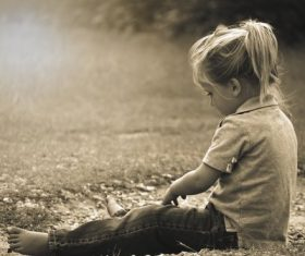 Little girl sitting on the ground playing Stock Photo