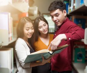 Male and female college students reading books in the library Stock Photo