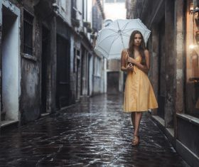 Outdoor hold up an umbrella yellow dress women Stock Photo