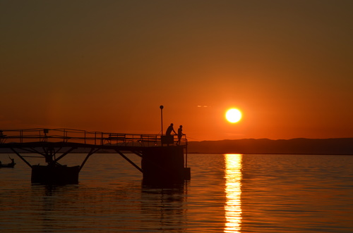 People fishing in the sunset Stock Photo