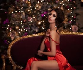 Red dress women indoors sitting on the sofa with christmas tree Stock Photo