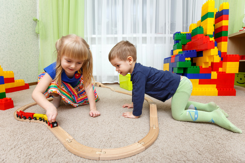 Sister and brother playing toy train Stock Photo
