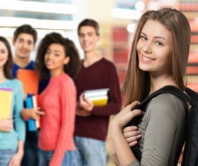 Smiling female college student and classmates Stock Photo