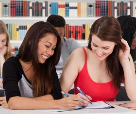 Smiling female college student writing homework Stock Photo