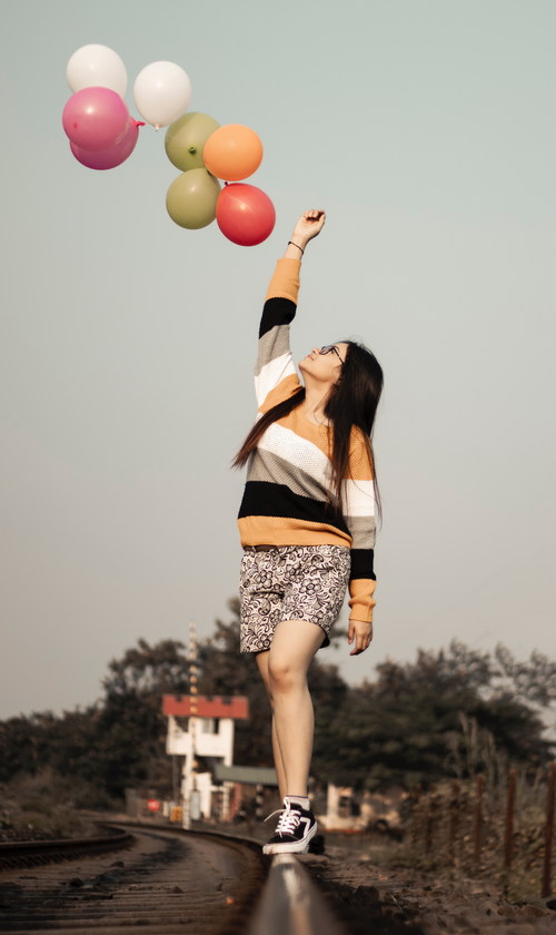 Standing high up woman putting balloons Stock Photo