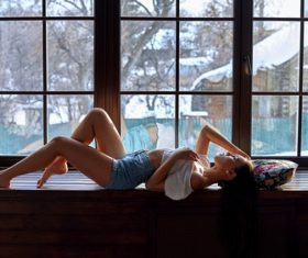 Stock Photo Woman lying on windowsill with snow scene outdoor