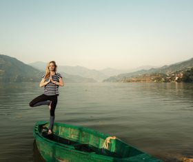 Stock Photo Woman standing on wooden boat with one leg