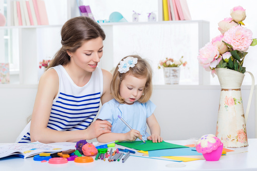 Stock Photo Young mother watching her daughter draw