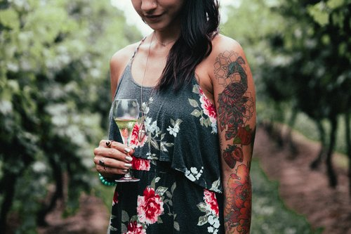 Tattooed woman tasting wine Stock Photo