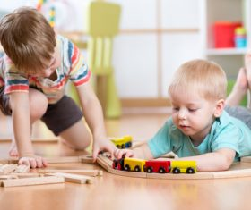 Two little boys playing with toy train Stock Photo