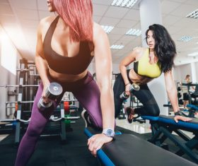 Two women doing dumbbell exercise in gym Stock Photo