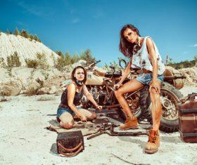 Two women repairing motorcycles Stock Photo