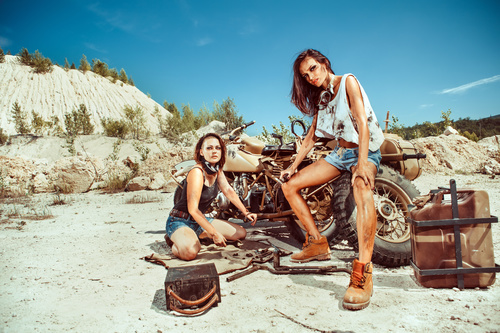 Two women repairing motorcycles Stock Photo