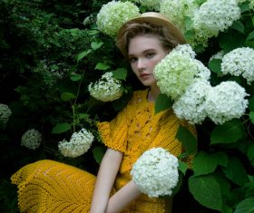 Wearing yellow dress women sitting in flowering shrubs Stock Photo