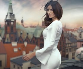 White dress woman standing high up looking at cityscape Stock Photo