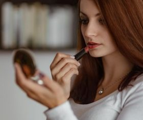Woman applying lipstick to small mirror Stock Photo