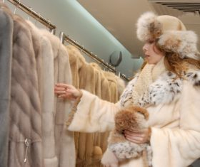 Woman buys choice of mink coat Stock Photo