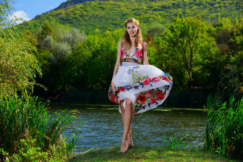 Woman in a floral dress stands by the river Stock Photo