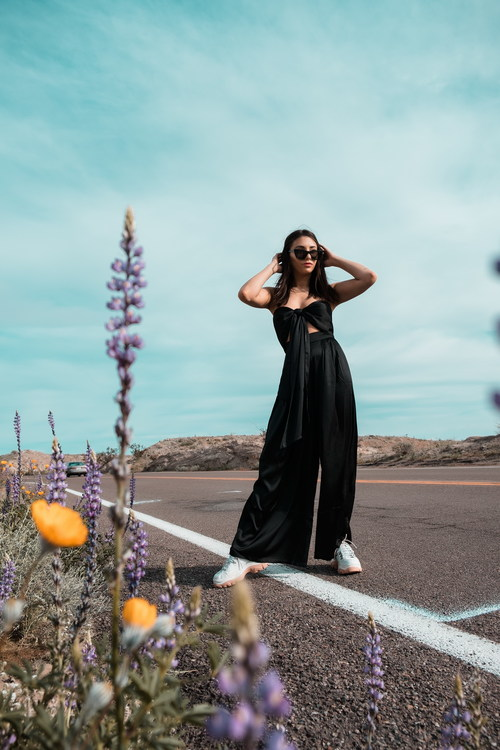 Woman in black long dress standing beside tar road Stock Photo