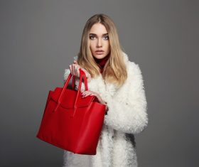 Woman in mink coat holding red handbag Stock Photo