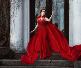 Woman in red dress and cloak outdoors Stock Photo
