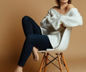 Woman in white sweater sitting on chair posing Stock Photo