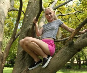 Woman on Squatting Tree Stock Photo