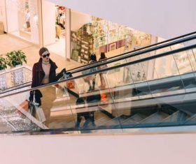 Woman on the escalator in the mall Stock Photo