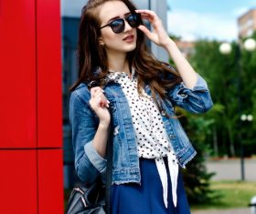 Woman on the street wearing sunglasses and denim jacket and short skirt Stock Photo