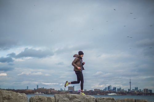 Woman running on the river embankment Stock Photo