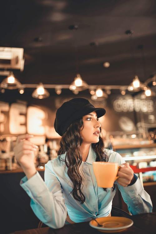 Woman sitting in cafe drinking coffee looking into the distance Stock Photo
