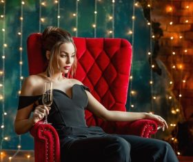 Woman sitting on red couch drinking champagne Stock Photo