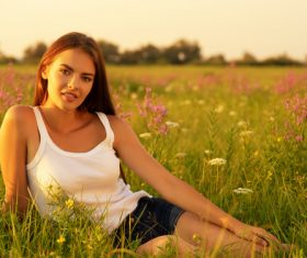 Woman sitting on the grass in the wild Stock Photo