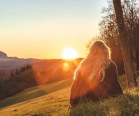 Woman sitting on the hillside looking at the rising sun Stock Photo