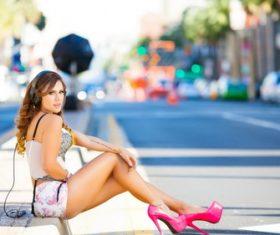 Woman sitting on the roadside wearing headphones Stock Photo