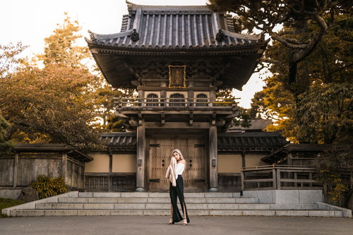 Woman standing in front of ancient temple Stock Photo