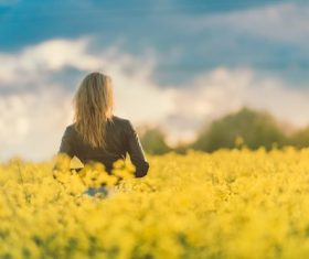 Woman standing in meadow of yellow flowers Stock Photo