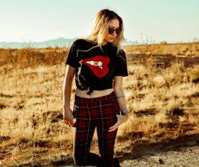 Woman wearing black t-shirt plaid pants posing Stock Photo