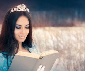 Woman wearing corolla reading book outdoors Stock Photo