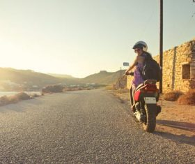 Woman wearing helmet riding a motorcycle Stock Photo