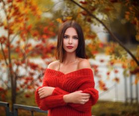 Woman wearing red sweater arms standing outdoors Stock Photo