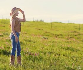 Woman with cowboy boots and hat standing in grass looking away Stock Photo