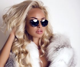 Woman with sunglasses wearing fur coat Stock Photo