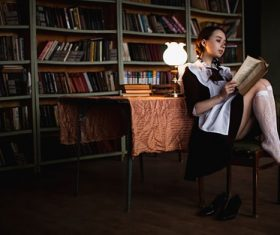 Women indoors reading under lamp light Stock Photo