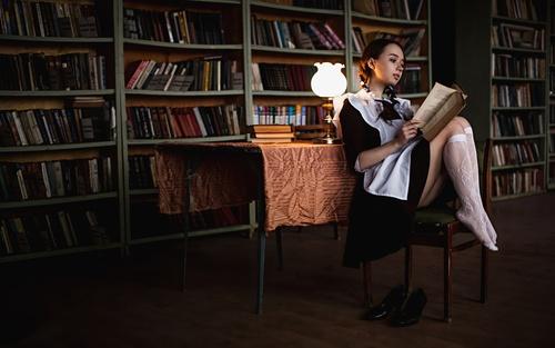 Women indoors reading under lamp light Stock Photo
