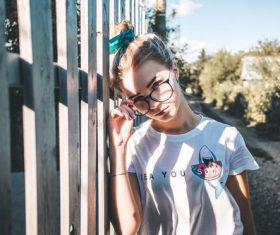 Young girl with glasses leans on the fence Stock Photo