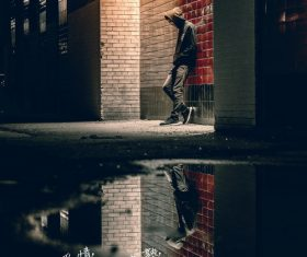 Young man standing under the street light Stock Photo