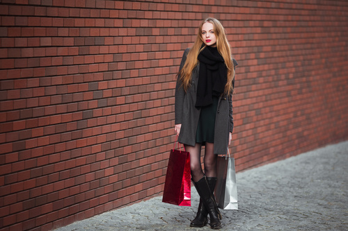 Young woman standing in front of red wall holding shopping bags Stock Photo 01