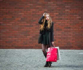 Young woman standing in front of red wall holding shopping bags Stock Photo 02