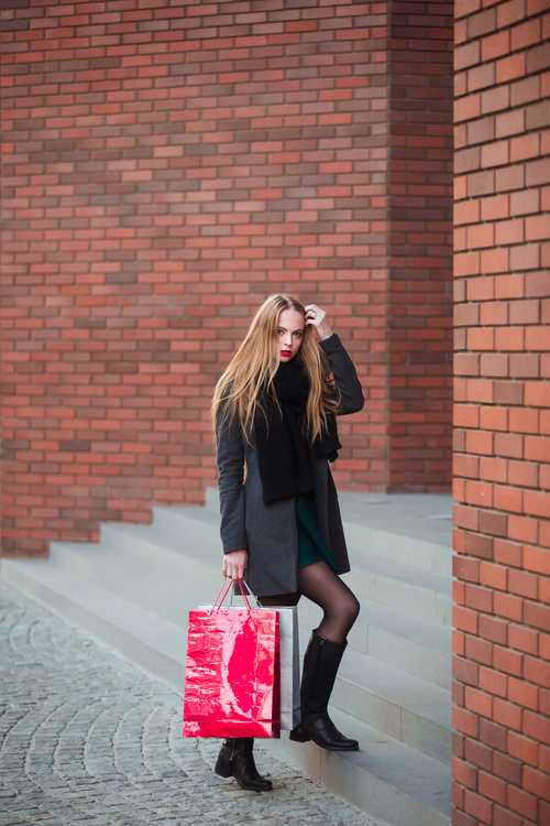 Young woman standing in front of red wall holding shopping bags Stock Photo 03